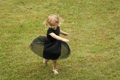 Menina com rotação do cabelo louro no vestido preto na grama fotos de stock royalty free