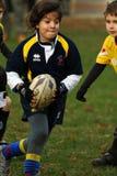 Menina com rugby do jogo revestimento azul/amarelo Imagem de Stock Royalty Free