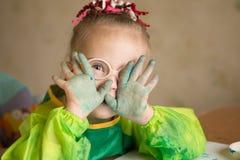 A menina com Síndrome de Down cobriu na pintura ao tirar fotografia de stock