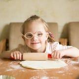 A menina com Síndrome de Down desenrola a massa fotografia de stock royalty free
