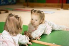 A menina com Síndrome de Down olha sua reflexão no espelho Imagens de Stock