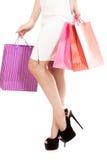 Menina com sacos de compras, close up nos pés fêmeas bonitos na WTI imagem de stock