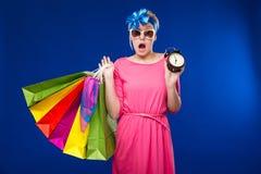 Menina com sacos e um despertador nas mãos Imagens de Stock