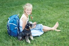 Menina com seu cão que senta-se na grama verde e no eBook lido imagens de stock royalty free