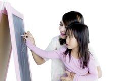 Menina com seu desenho da mãe com giz foto de stock