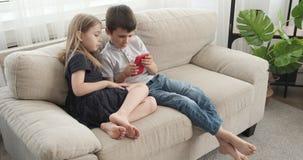 Menina com seu irmão que joga o jogo usando o telefone celular no sofá vídeos de arquivo