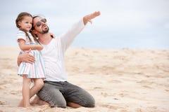 Menina com seu pai feliz no oceano da costa Pontos a algo Fotos de Stock Royalty Free