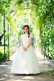 Menina com seu primeiro vestido do comunhão fotografia de stock