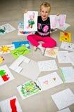 Menina com seus desenhos no assoalho imagem de stock