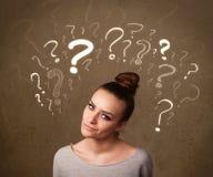 Menina com símbolos do ponto de interrogação em torno de sua cabeça Imagens de Stock