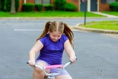 a menina com sua menina da criança de 5 anos da bicicleta A está montando uma bicicleta em um trajeto através de um parque Fotografia de Stock