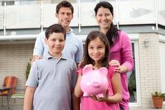 Menina com sua família que prende um banco piggy Imagens de Stock Royalty Free