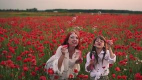 Menina com sua mãe que joga com bolhas de sabão no campo de florescência das papoilas, movimento lento filme