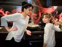 Menina com sua mãe na cozinha no fogão Fotos de Stock Royalty Free
