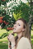 Menina com suportes de fluxo do cabelo perto de um ramo com Rowan imagem de stock royalty free
