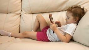 Menina com a tabuleta no sofá vídeos de arquivo
