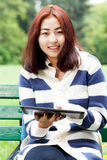 Menina com a tabuleta que senta-se no banco Imagens de Stock Royalty Free