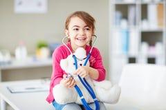 Menina com teddybear e o estetoscópio Imagem de Stock