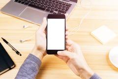 Menina com telefone celular com tela vazia, portátil, fones de ouvido e p Imagens de Stock