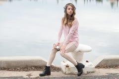 Menina com telefone celular e fones de ouvido Fotografia de Stock