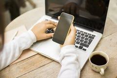 Menina com telefone celular, o portátil e a xícara de café vazios fotografia de stock