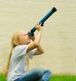 Menina com telescópio Fotografia de Stock
