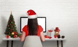 Menina com trabalho do chapéu de Santa no computador no tempo do Natal fotografia de stock