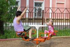 A menina com tranças e paizinho gerencie no carrossel foto de stock