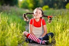 A menina com tranças imagina o verão na natureza imagens de stock