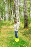 Menina com um brinquedo favorito na floresta em um dia de verão Vista traseira Imagem de Stock Royalty Free