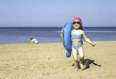 Menina com um círculo na praia do mar Fotos de Stock Royalty Free