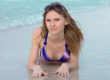 A menina com um cabelo de fluxo encontra-se na areia com os óculos de sol violetas na cabeça atrás dela o mar Fotos de Stock Royalty Free
