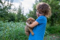 Menina com um cachorrinho em seus braços foto de stock