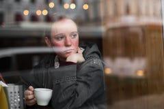 Menina com um café que senta-se em um café imagem de stock royalty free