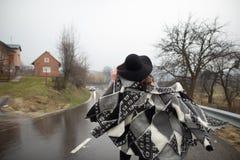 Menina com um chapéu negro que anda ao longo da estrada em um dia chuvoso imagens de stock royalty free