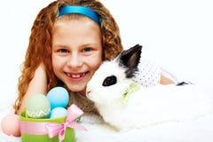a menina com um coelho de coelho tem um easter no carpe branco Imagens de Stock