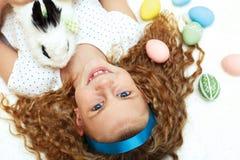 a menina com um coelho de coelho tem um easter no carpe branco Fotografia de Stock Royalty Free