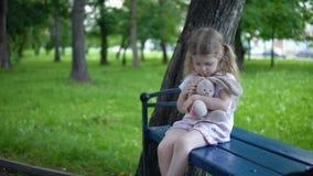 Menina com um coelho do brinquedo que senta-se em um banco de parque em um dia nebuloso filme