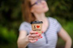 Menina com um copo de papel com mundo escrito imagem de stock royalty free