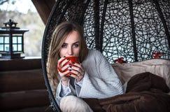 Menina com um copo do chá em uma cadeira confortável Fotos de Stock Royalty Free