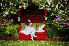 Menina com um copo do chá no jardim Imagens de Stock Royalty Free