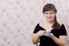 Menina com um copo em suas mãos Imagens de Stock