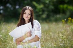 A menina com um descanso na grama fresca da mola Fotos de Stock