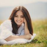 A menina com um descanso na grama fresca da mola Foto de Stock