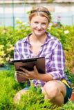 A menina com um dobrador analisa o crescimento e o desenvolvimento das plantas Fotos de Stock