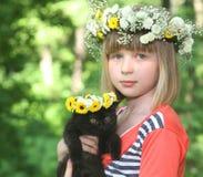 A menina com um gatinho preto. Fotos de Stock