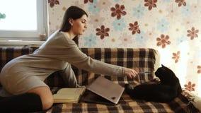 Menina com um gato que encontra-se no sofá video estoque