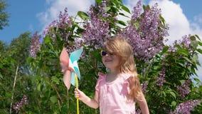 Menina com um girândola em um parque ao lado de um lilás de florescência na primavera filme