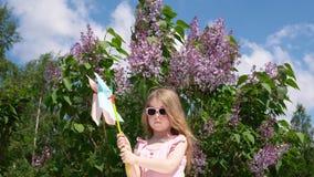 Menina com um girândola em um parque ao lado de um lilás de florescência na primavera video estoque
