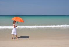 Menina com um guarda-chuva no Sandy Beach imagem de stock